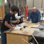 Volunteer Frank Gllant oversees students as they work on a woodworking project.