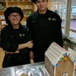 Culinary students display the gingerbread house they are making for their class project.